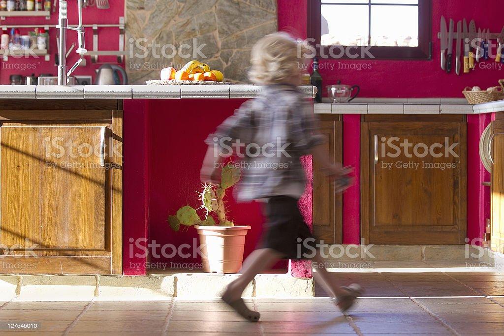 Boy running in kitchen stock photo