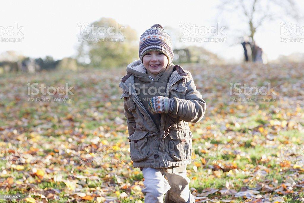 Menino correndo no parque no outono foto royalty-free