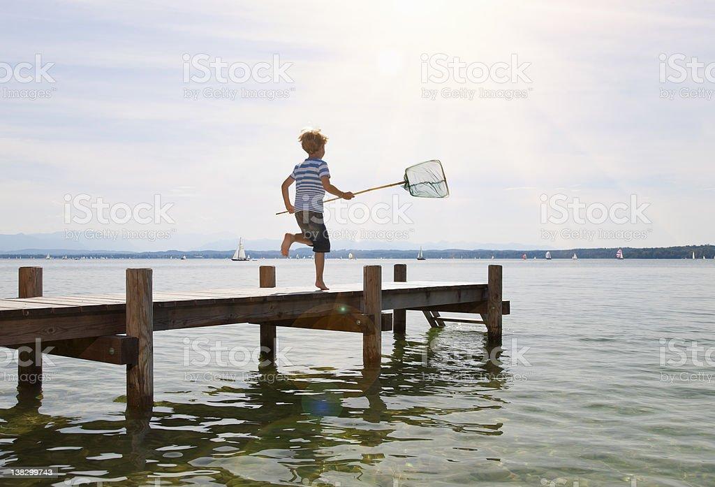 Boy running on dock with fishing net stock photo