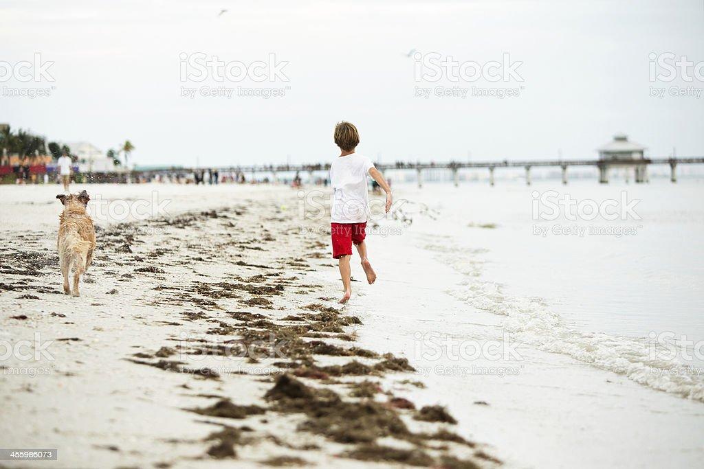 Boy Running on Ocean Beach with Golden Retriever Dog stock photo