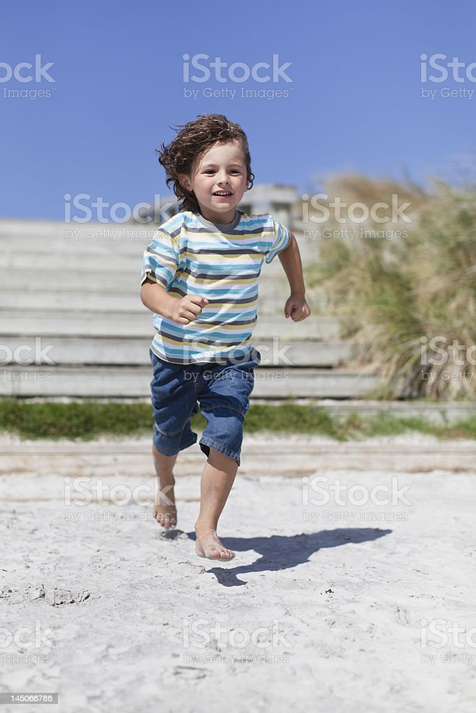 Boy running on sandy beach stock photo