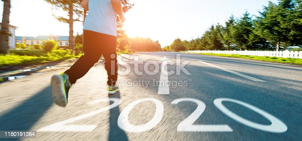 171150458istockphoto Boy running on the road with writing Number 2020 1150191264
