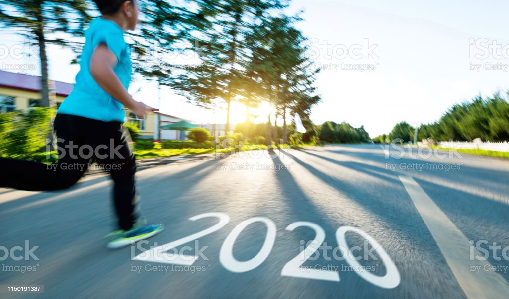 Boy running on the road with writing Number 2020.