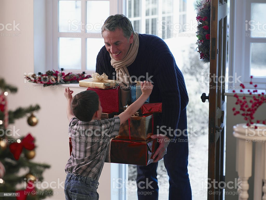 Boy running to father holding Christmas gifts in doorway stock photo