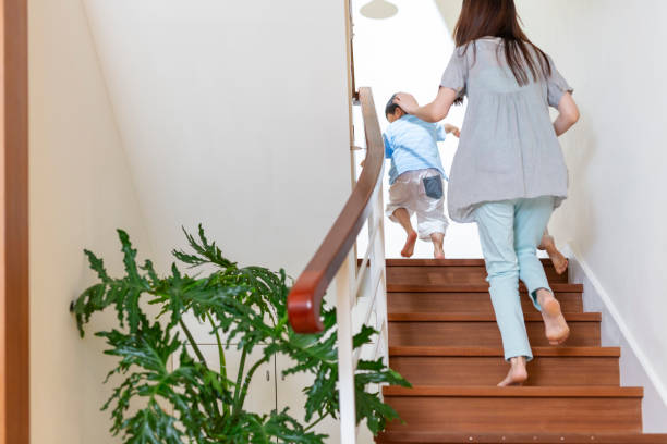 Boy Running Upstairs With His Mother stock photo