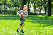 Boy Having Fun Running With Rugby Ball In The Park