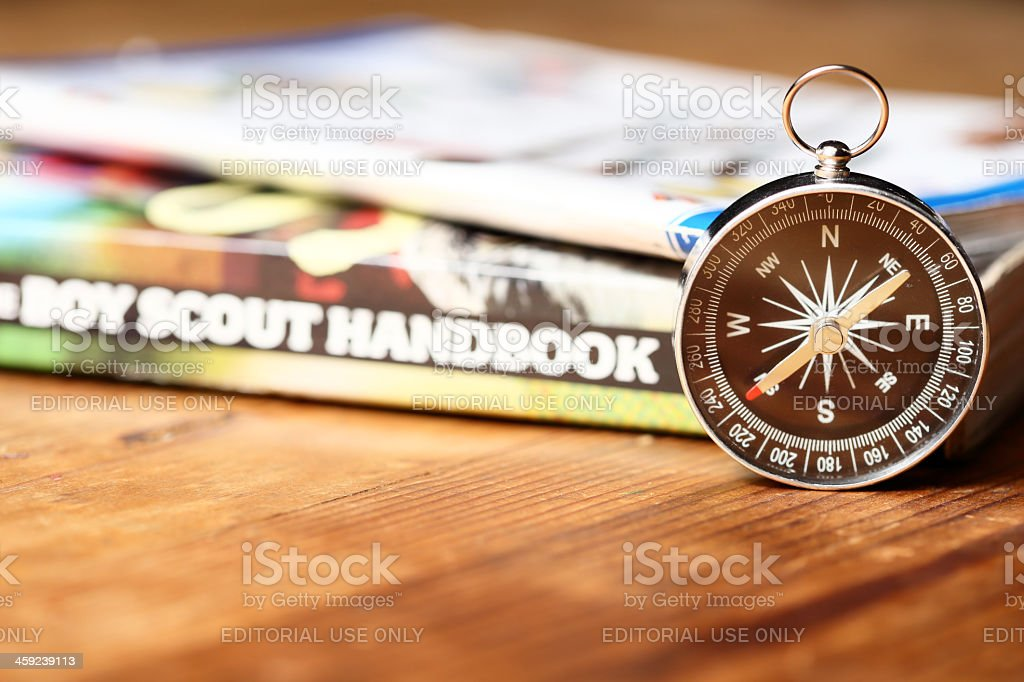 Boy Scout Handbook with Compass on Wood Table stock photo