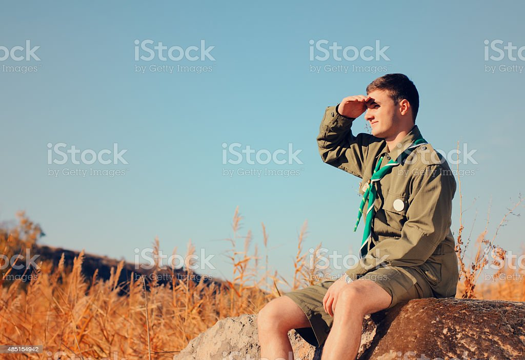 Boy Scout Sitting on Rock Watching Over the Field stock photo