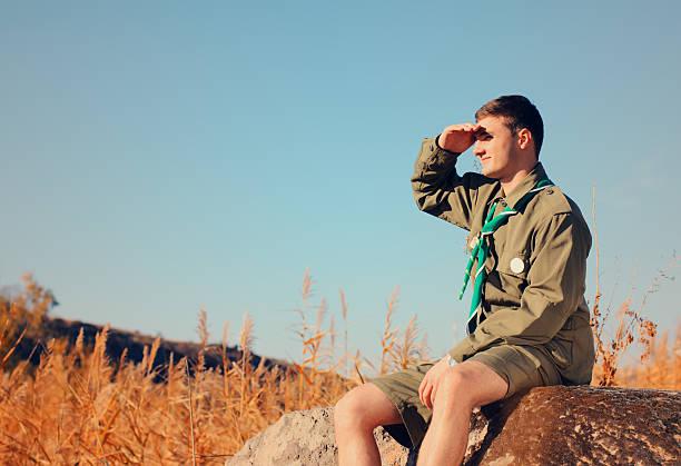 boy scout sentado en rock frente al campo - boy scout fotografías e imágenes de stock