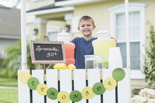 Boy selling lemonade in front yard A boy with a lemonade stand in his front yard. He is smiling confidently and looking at the camera. lemonade stand stock pictures, royalty-free photos & images