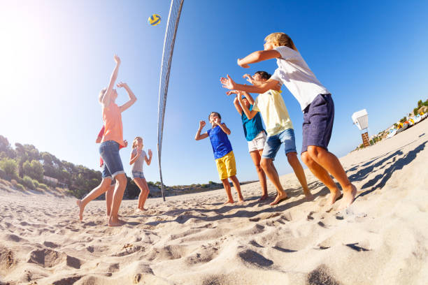 Boy serving the ball during beach volleyball match stock photo