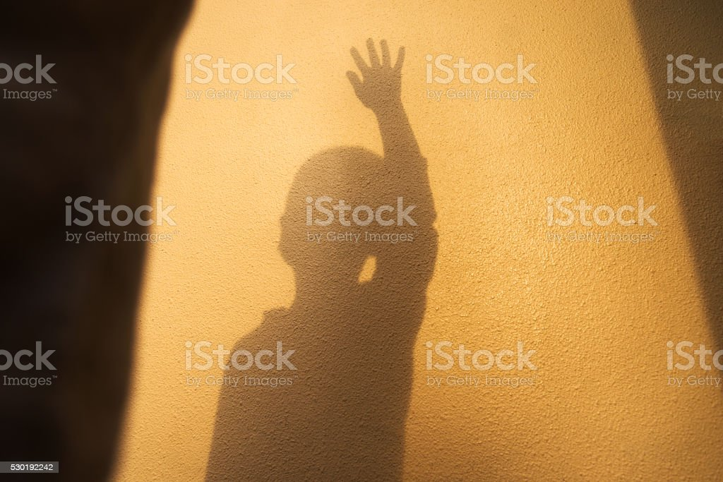 Boy shadow with arms raised stock photo