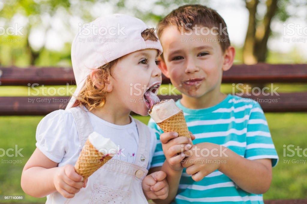 niño compartir el helado con su hermana - foto de stock
