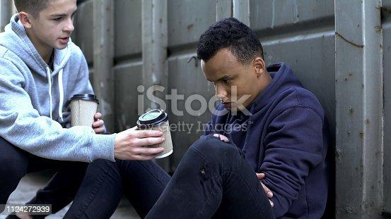 istock Boy sharing warm coffee with frozen homeless teenager, charity volunteer 1124272939