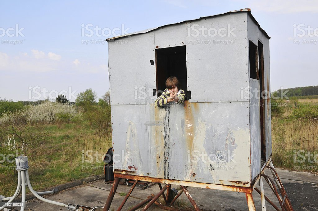 Boy shooting  in worn guard house at former DDR royalty-free stock photo