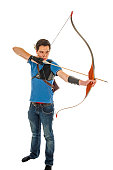 Boy with blue shirt and jeans aiming with a longbow isolated in white