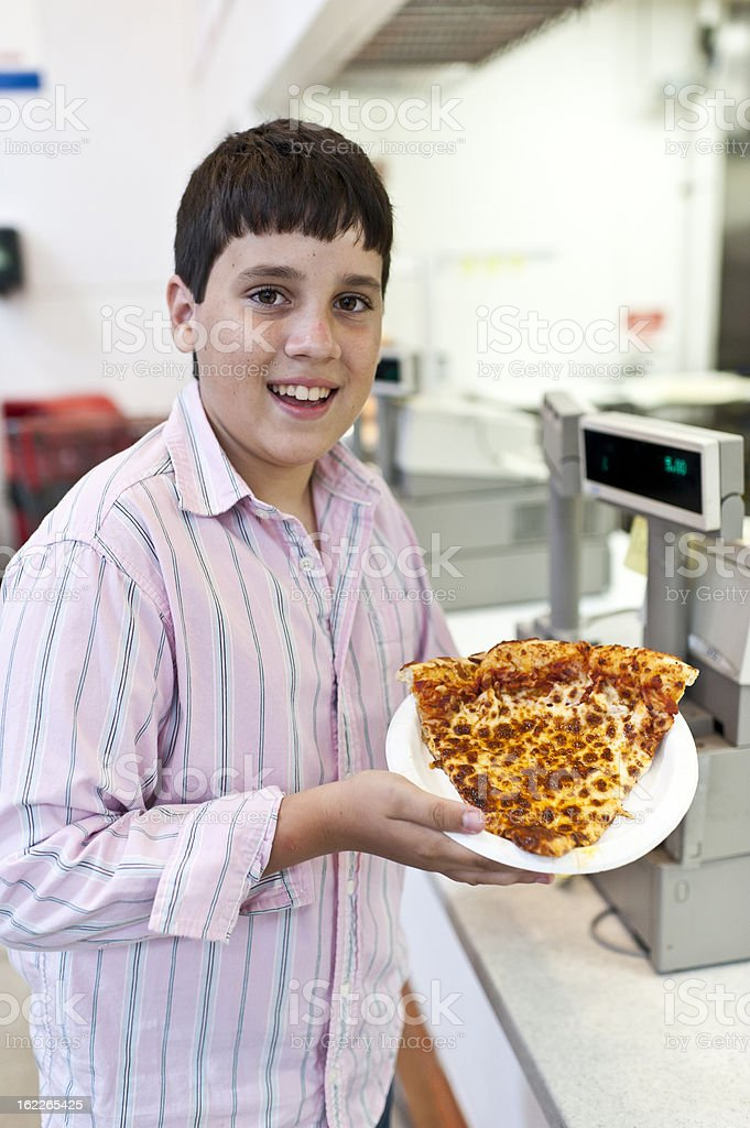 boy showing an slice of pizza at restaurant royalty-free stock photo