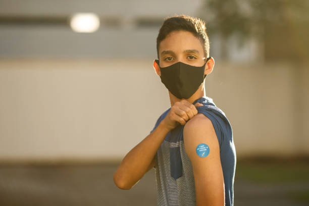 Boy showing his covid 19 vaccine badge stock photo