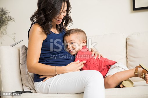 Cute little boy showing love towards unborn baby in mother's tummy at home