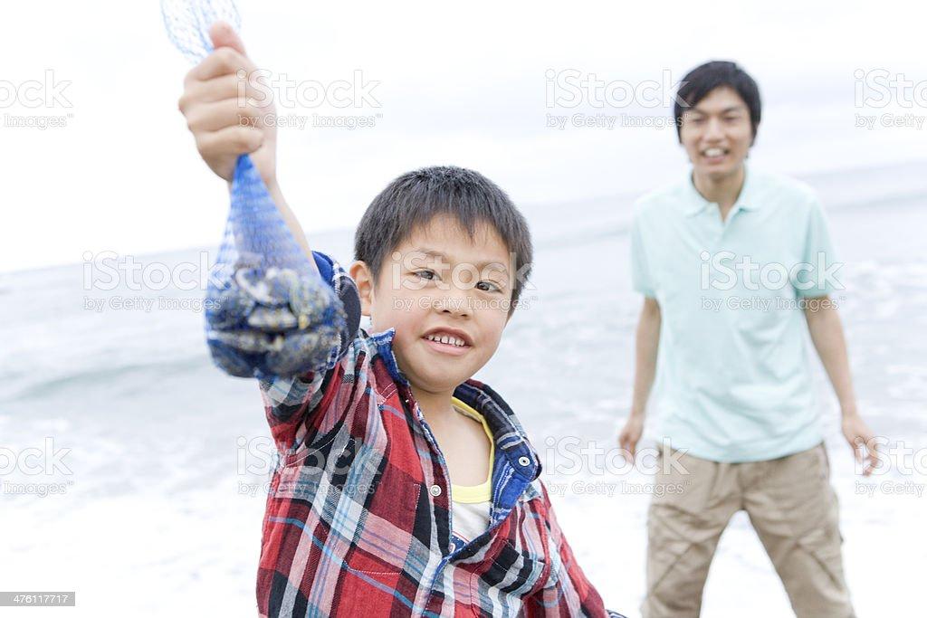 少年表示貝で獲れたばかりのシーシェル掘る ストックフォト