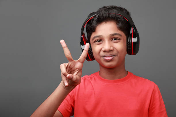Boy shows cheering gestures while listening to music stock photo