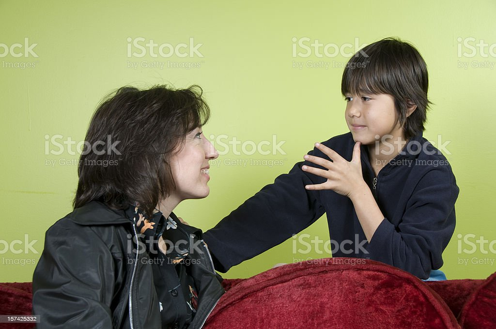 Boy signing Mom in ASL stock photo