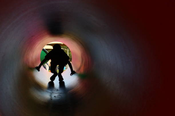 Boy silhouette in the pipe Boy walking out of the pipe at the playground confined space stock pictures, royalty-free photos & images