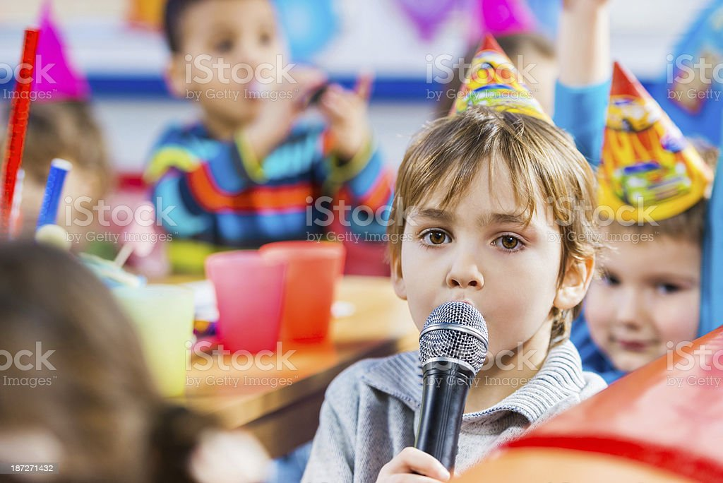 Boy singing on a birthday party. stock photo