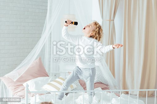 istock Boy singing, standing on bed 656169096