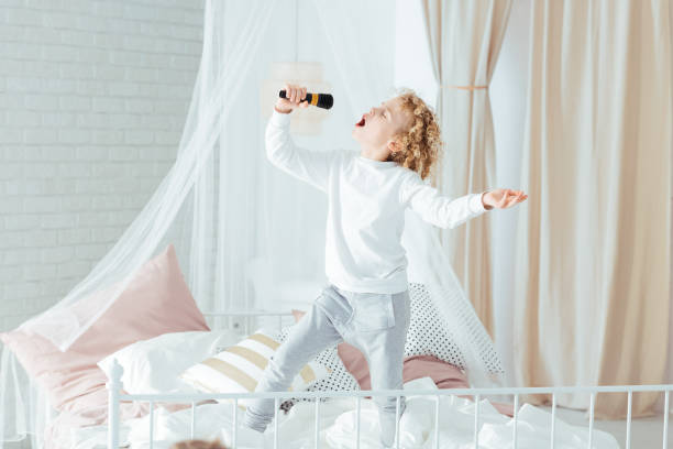 Boy singing, standing on bed stock photo