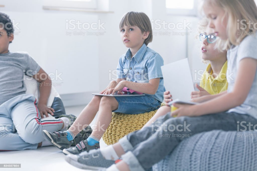 Boy sits in a group of children stock photo