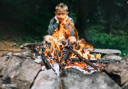 istock Boy sits near campfire in forest 961829922