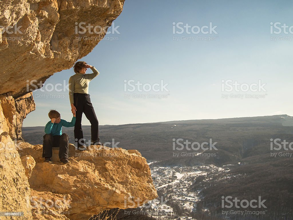 Boy sits on rock near the mother stock photo