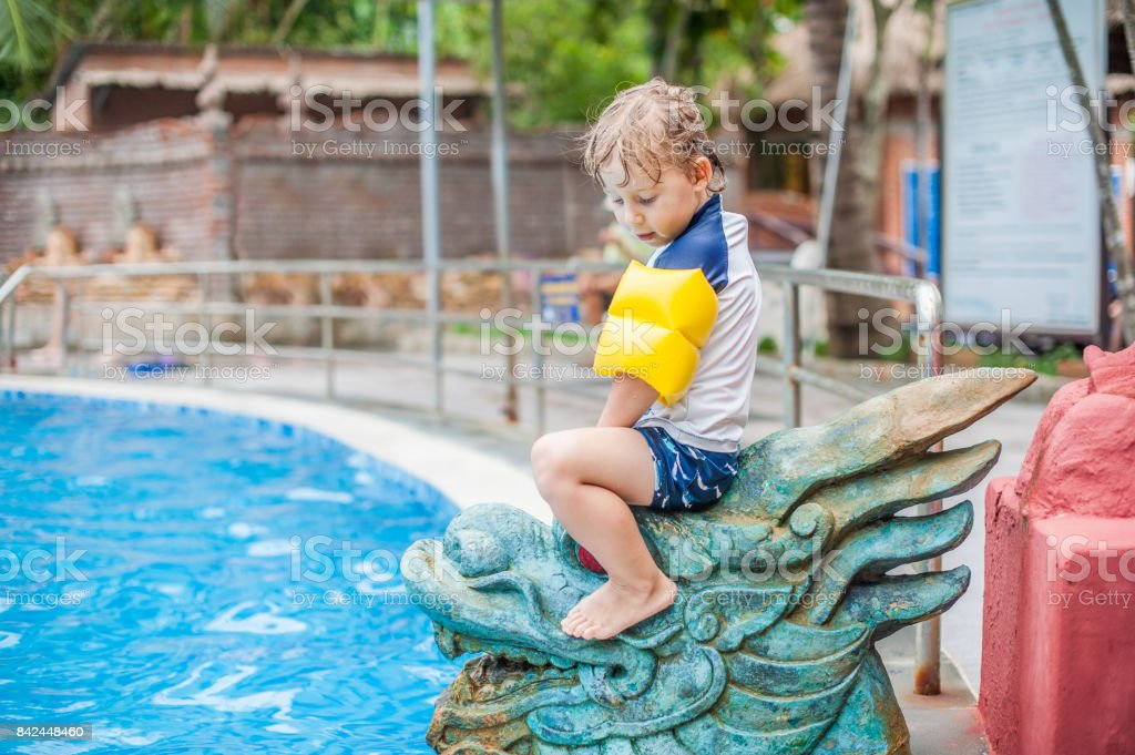A boy sits on the Asian statue stock photo