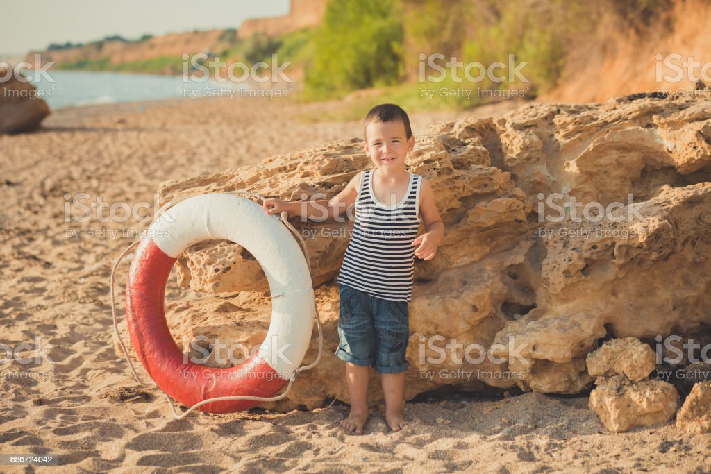aabfe6e7a A boy sits on the beach in a striped shirt with a marine lifebuoy,  liferound. A boy sits on the sand on a beautiful beach. Beautiful beach and  sea - Stock ...