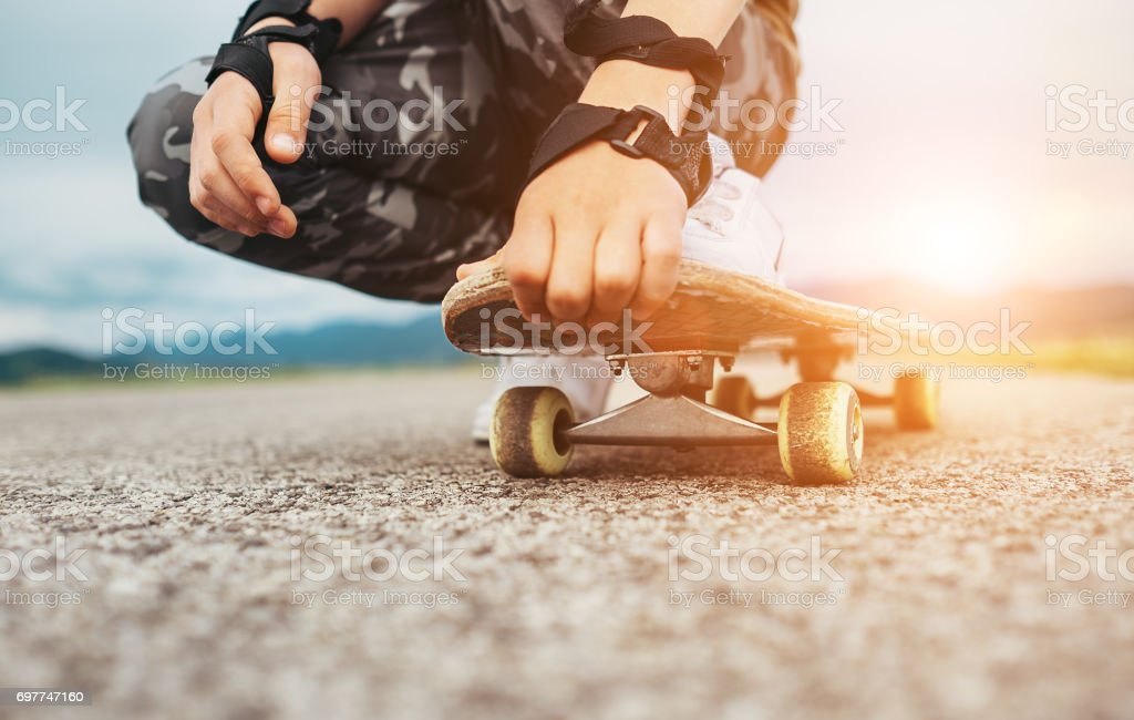 Boy sits on the skateboard legs and hands closeup image stock photo