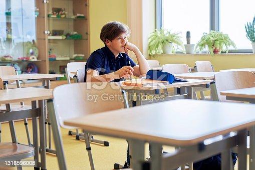 istock Boy sitting alone in empty classroom 1316596008