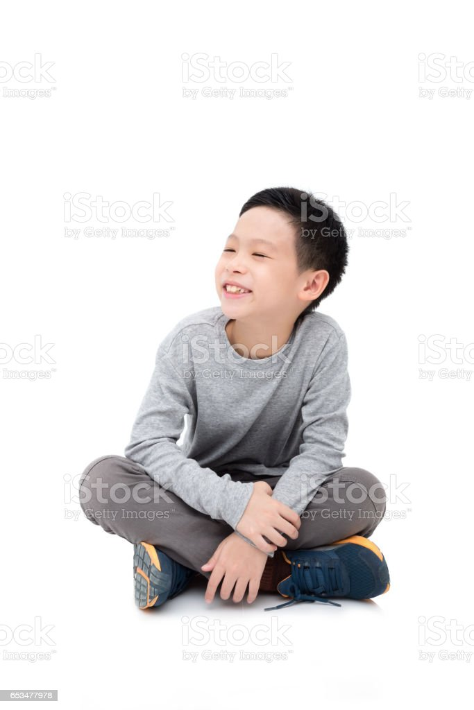 boy sitting and smiles over white background stock photo
