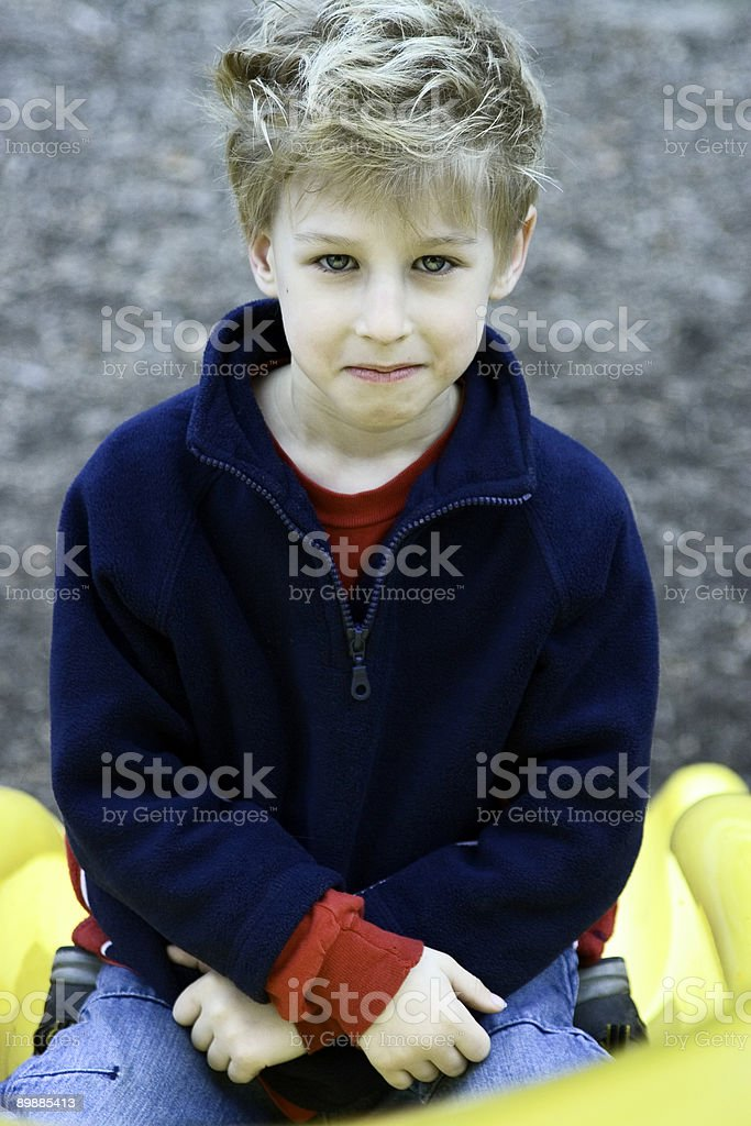 Boy Sitting at Bottom of Slide, Color Version royalty-free stock photo