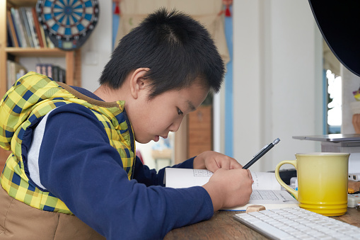 Asian boy around 10 years old playing Sudoku game on his desk