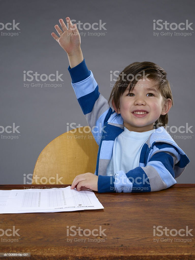 Boy (2-3) sitting at desk, raising hand, smiling royalty-free stock photo