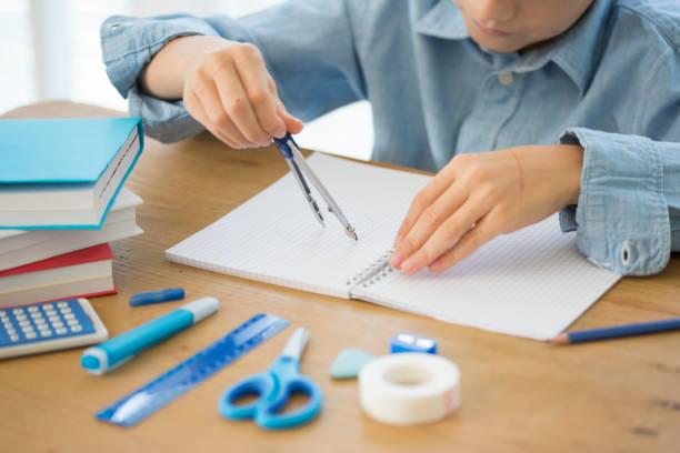 Niño sentado en el escritorio haciendo su tarea de geometría - foto de stock