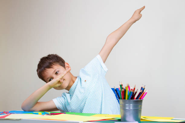 Boy sitting at the table and shows dab gesture stock photo