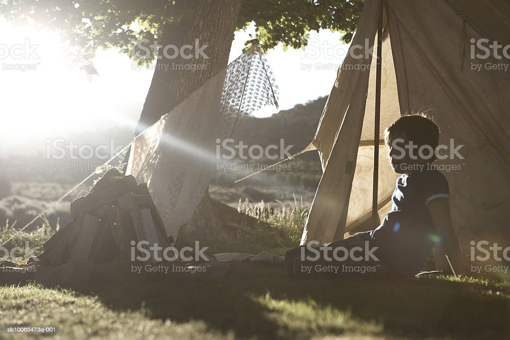 Boy (10-11) sitting by camping tent, side view royalty-free stock photo
