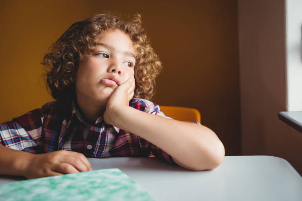 Boy sitting down on his chair and dreaming stock photo