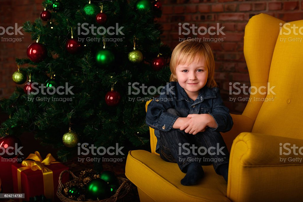 boy sitting in a chair near the Christmas tree stock photo