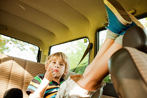 Boy sitting in back seat of car stock photo