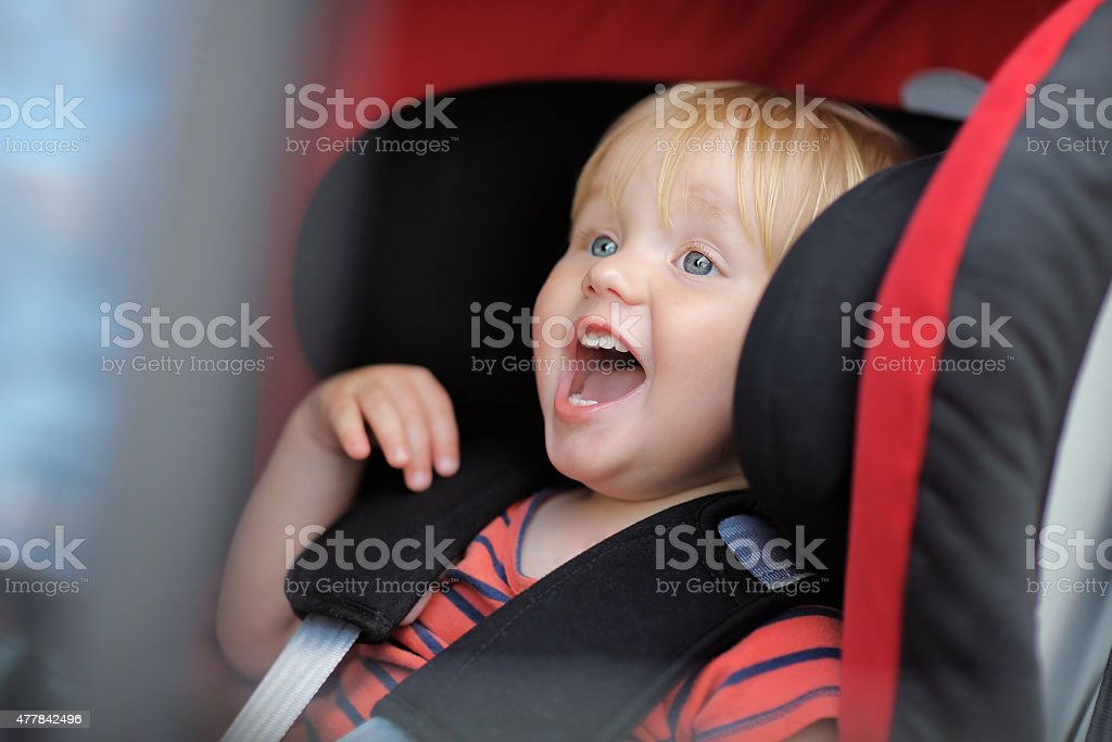 Boy sitting in car seat Emotional toddler boy sitting in car seat 12-17 Months Stock Photo