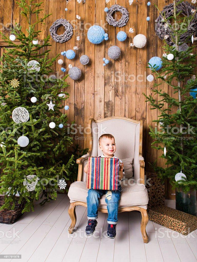 Boy  sitting in  chair near Christmas tree stock photo