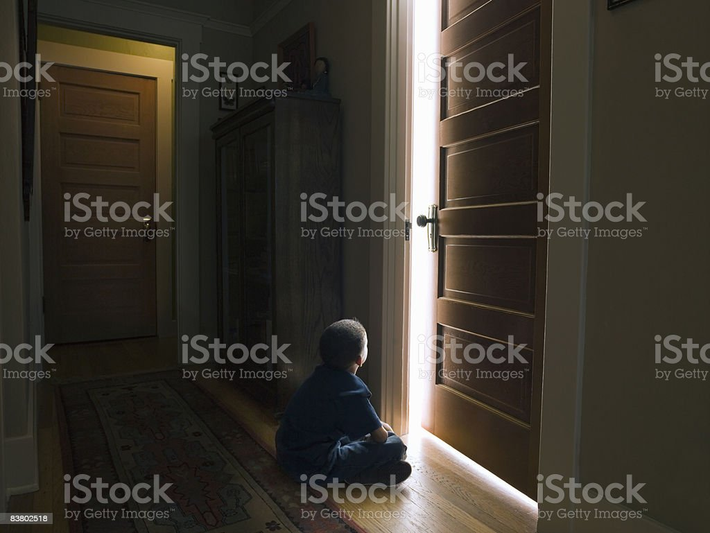 Boy sitting in front of door with light coming out royalty-free stock photo